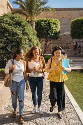 Three happy female friends walking around in a formal garden - MPPF00149