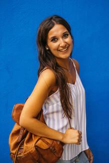 Portrait of beautiful young woman with backpack at a blue wall - MPPF00179