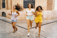 Three happy female friends running in the city - MPPF00182