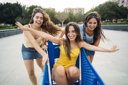 Three playful female friends with shopping cart in the city - MPPF00191
