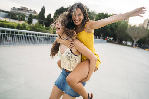 Playful young woman carrying friend piggyback - MPPF00194