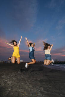 Three carefree female friends jumping on the beach at sunset - MPPF00200