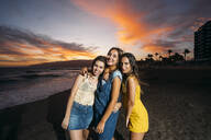 Portrait of three happy female friends on the beach at sunset - MPPF00203