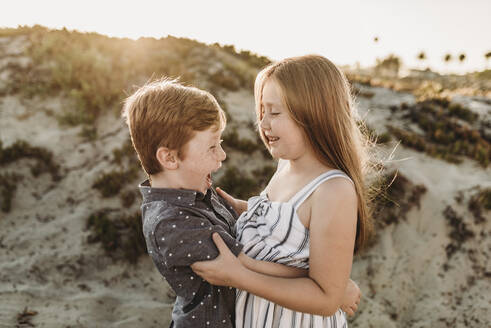 Side view of young brother and sister hugging and laughing at beach - CAVF65546