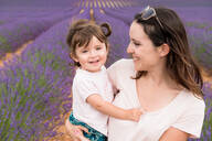 Happy mother and daughter walking among lavender fields in the summer - CAVF65570