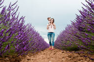 Mother and daughter walking among lavender fields in the summer - CAVF65573