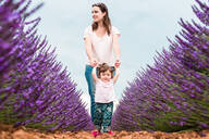 Happy mother and daughter walking among lavender fields in the summer - CAVF65576
