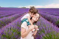 Happy woman and little girl walking among lavender fields in summer - CAVF65579