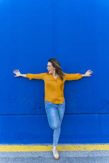 Young surprised woman leaning on blue wall - AFVF04063