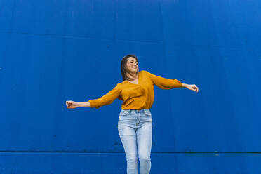 Young dancing woman in front of a blue wall - AFVF04066