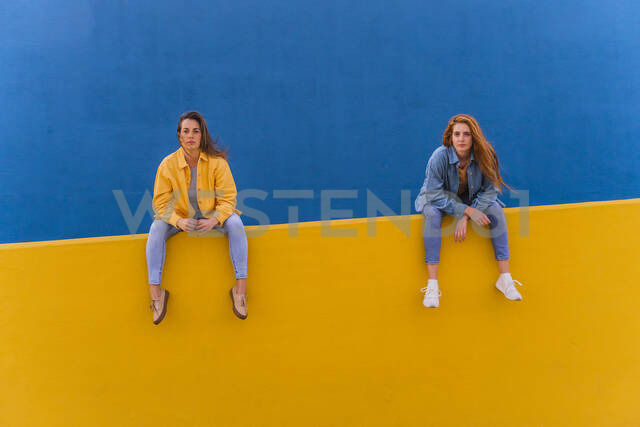 Young women sitting on an orange wall - AFVF04072 - VITTA GALLERY/Westend61