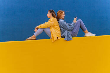 Young beautiful carefree women sitting on an orange wall, redheaded woman using smartphone - AFVF04075