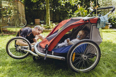 Father repairing bicycle trailer with baby boy sitting in it - MFF04908