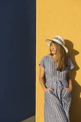 Woman standing in front of yellow and blue walls - AHSF00951