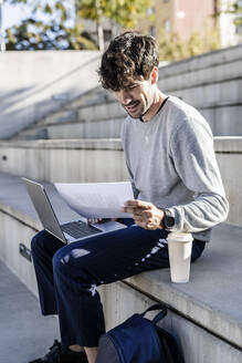 Man sitting on outdoor stairs using laptop and reviewing paper - GIOF07239