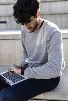 Man sitting on outdoor stairs using laptop and checking the time - GIOF07245