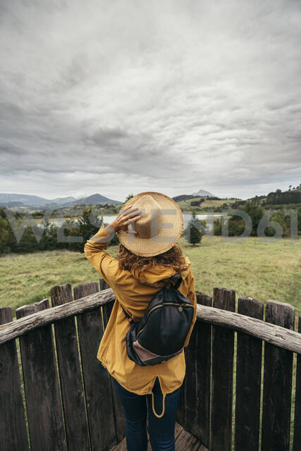 Young woman wearing yellow coat and backpack with a hand holding a hat in her head looking the lake landscape on top of a wood balcony - MTBF00002 - Mikel Taboada/Westend61