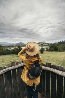 Young woman wearing yellow coat and backpack with a hand holding a hat in her head looking the lake landscape on top of a wood balcony - MTBF00002