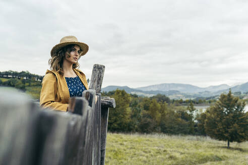 Young curly haired woman wearing a hat, yellow coat and blue t-shirt looking the mountain landscape - MTBF00005