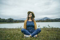 Young smiling woman wearing yellow coat sitting on a meadow and looking up - MTBF00014