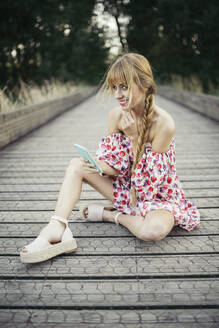 Portrait of smiling young woman with smartphone sitting on boardwalk in summer - MTBF00023