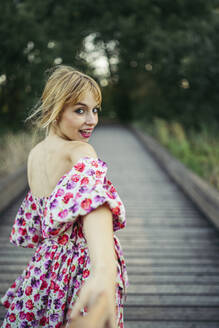 Portrait of happy young woman wearing summer dress with floral design on boardwalk holding hand - MTBF00032