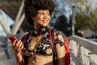Female Afro-American with headphones and smartphone listening music - ERRF01724