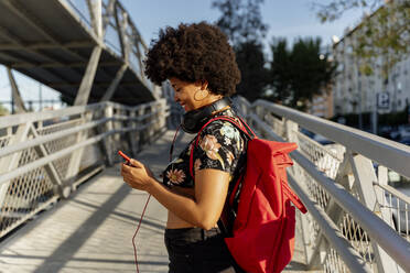 Female Afro-American with headphones and smartphone listening music - ERRF01727