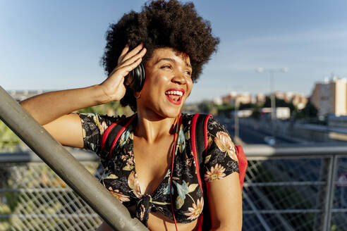 Female Afro-American with headphones listening music, looking sideways - ERRF01739
