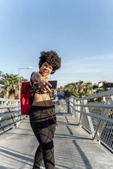 Female Afro-American with headphones and smartphone listening music - ERRF01745