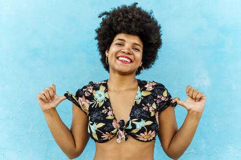 Smiling Afro-American woman in front of a blue wall - ERRF01763