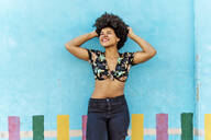 Smiling Afro-American woman in front of a blue wall with hands in hair - ERRF01766