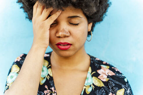 Portrait of Afro-American woman, hand on forehead, blue wall in the background - ERRF01769