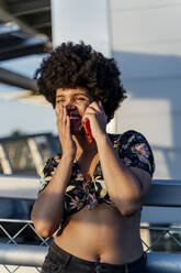 Smiling Afro-American woman with red smartphone - ERRF01784