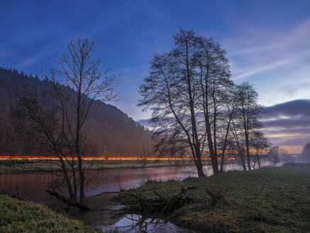 Germany, Bavaria, Silhouettes of trees against vehicle light trails stretching along shore of Naab river at dusk - HUSF00085