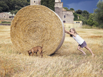 Smiling little girl rolling hay bale - XCF00291
