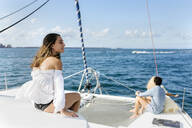 Three young friends enjoying a summer day on a sailboat - MGOF04147