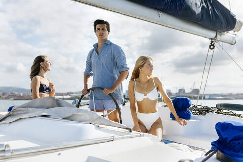 Three young friends enjoying a summer day on a sailboat - MGOF04156