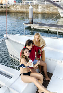 Three young friends enjoying a summer day on a sailboat, taking a selfie - MGOF04204