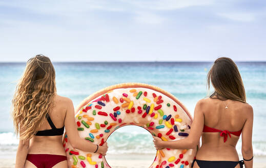 Two young women standing in front of the sea holding a big inflatable ring - EPF00603