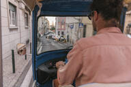 View from behind of a tuk tuk driver in the city, Lisbon, Portugal - AHSF00985