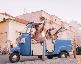 Tuk tuk driver providing tour of the city to a tourist, Lisbon, Portugal - AHSF00991