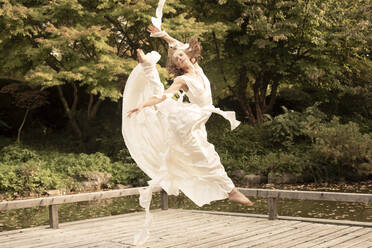 Ballerina wearing white dress and jumping on wooden jetty - FCF01825