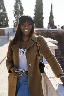 Portrait of a smiling female tourist outdoors - GIOF07273