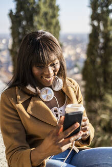 Smiling female tourist looking at her smartphone outdoors - GIOF07288