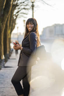 Smiling businesswoman standing at rivershore - GIOF07303