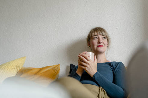 Portrait of woman sitting on the couch with cup of coffee looking at distance - KNSF06824