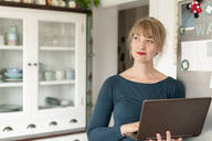 Portrait of woman standing with laptop in the kitchen looking at distance - KNSF06845