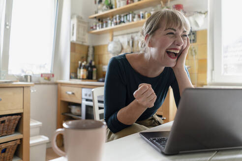 Portrait of woman sitting in the kitchen with laptop crying for joy - KNSF06854
