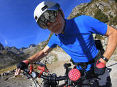 Senior man with his electric mountain bike in the Alps - LAF02385